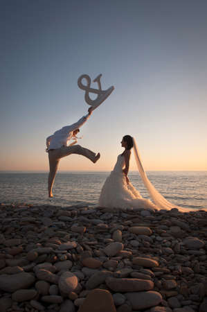 Young happy bridal couple having fun at edge of water with a large sign photo
