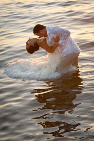 Beautiful couple dancing in water with sunlight reflections Standard-Bild