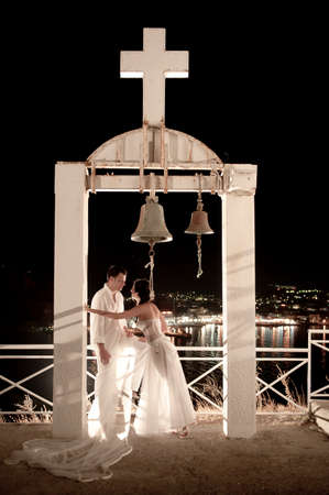 church bell: Night view of young newly wed couple under church bell archway with city lights