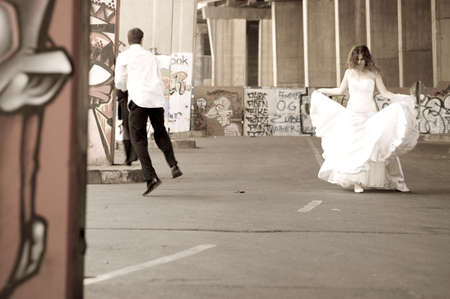 newly: Young happy newly wed couple walking outdoors between graffitti pillars