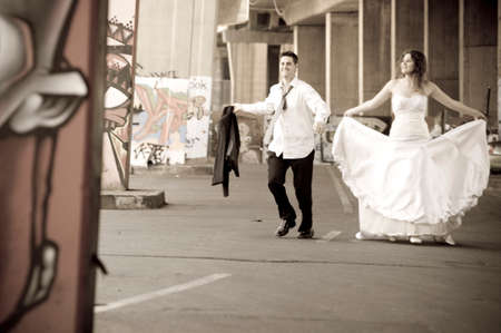 wed: Young happy newly wed couple walking outdoors between graffitti pillars
