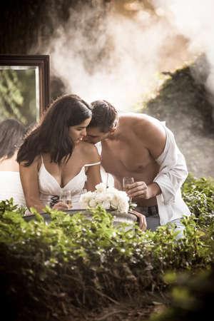 enamorados besandose: Beautoful de enamorados pareja de ba�o y fliting al aire libre en el jard�n a trav�s de la niebla Foto de archivo