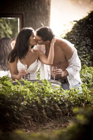 Beautoful in love couple bathing and fliting outdoors in garden through mist