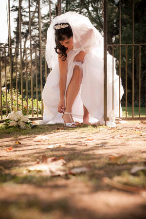 heel strap: Pretty bride leaning down to fix her shoe fitting against iron gate