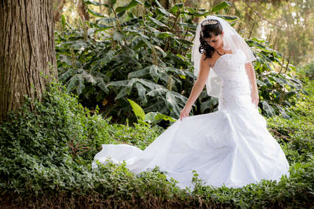 bridal gown: Young beautiful bride wearing her bridal gown in green garden playing with skirt Stock Photo