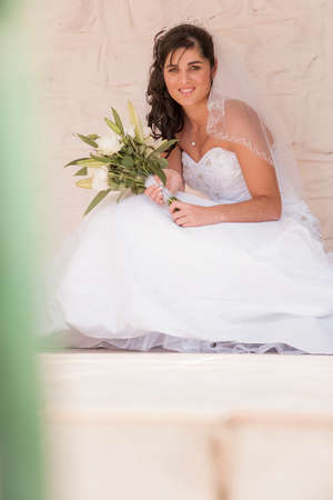 heel strap: Beautiful young bride in wedding dress with bouquet of flowers