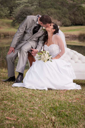 Young bridal couple kissing on beach outdoors in garden photo