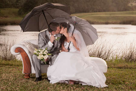 Young bridal couple sitting on beach outdoors in garden under large umbrellas photo