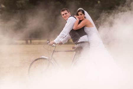 Frisch vermählte Braut und Bräutigam reitet ein vinatage Fahrrad durch nebligen Feld Standard-Bild - 37163861