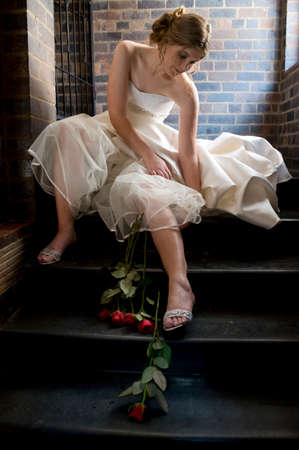 Young beautiful bride sitting with red roses fiddling with skirt layers