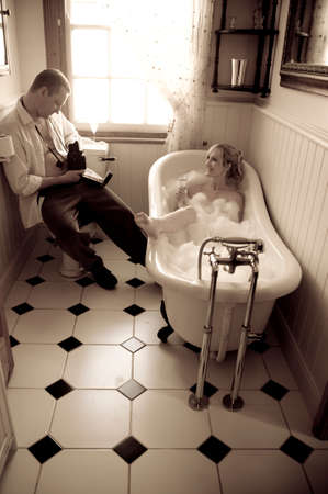 Young happy couple flirting in bathroom with vintage camera photo