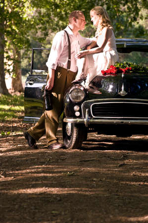 Happy attratcive couple outdoors with vintage car and red roses Zdjęcie Seryjne