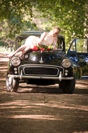 Happy attratcive couple outdoors with vintage car and red roses Standard-Bild