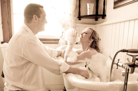 Young happy couple flirting in bathroom kising with bubble bath photo