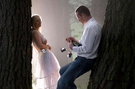 mid adult couple: attractive young couple leaning against tree trunk in misty forest