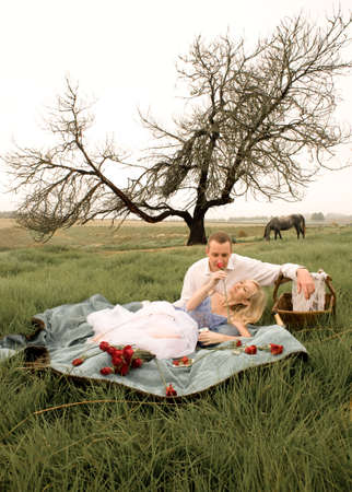 Happy young couple having a romantic picnic outdoors in green field photo