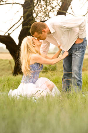 horse laugh: Happy young couple having a romantic kiss outdoors in green field