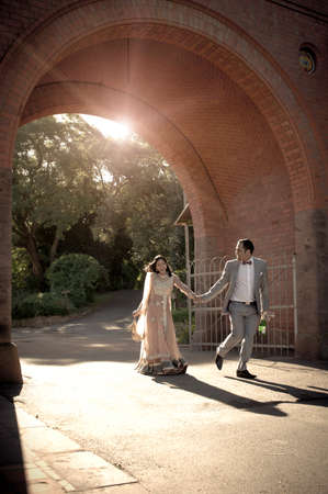 Young attractive Indian couple walking under brick archway holding hands