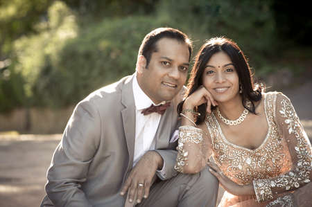 Young Beautiful Indian couple relaxing together outdoors in formal wear