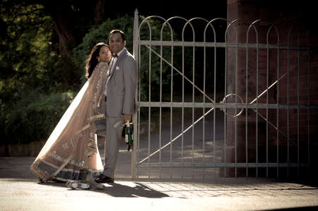 Young happy Indian couple flirting against iron gate