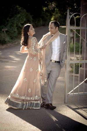 Junge glückliche indische Paar Flirten gegen Eisentor Standard-Bild - 37211932