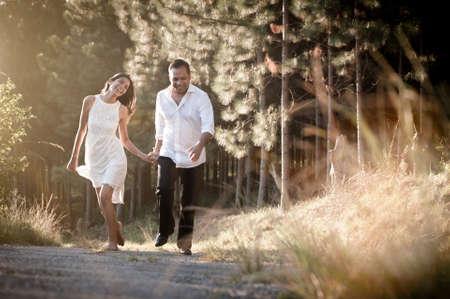 Glückliche indische Paare entlang Feldweg mit goldenem Licht durch lange Gras Standard-Bild - 37163803
