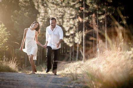 Happy Indian couple running along dirt road with golden light through long grass