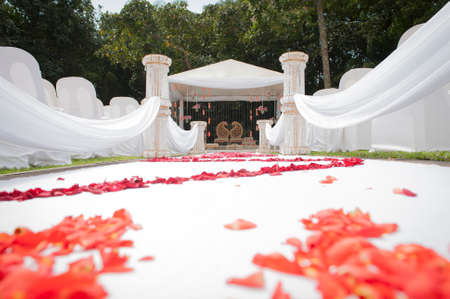 low angle view of wedding ceremony aisle with rose petals and white d?cor 版權商用圖片