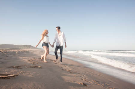 Young beautiful couple hanging out together at the beach photo