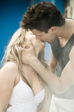 parejas jovenes: Joven pareja bes�ndose en las escaleras del edificio pintado de azul Foto de archivo