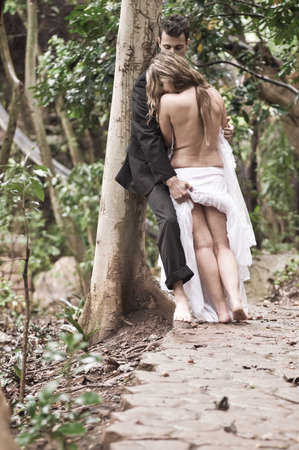 Good looking sensual couple kissing in forest of trees