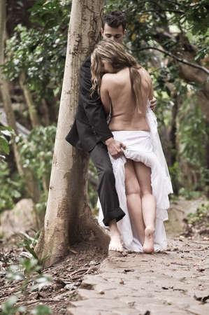 parejas caminando: Bueno buscando pareja sensual besando en el bosque de los �rboles Foto de archivo