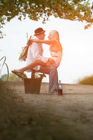 Young attractive couple sitting flirting together on dirt road at sunrise with basket full of flowers photo