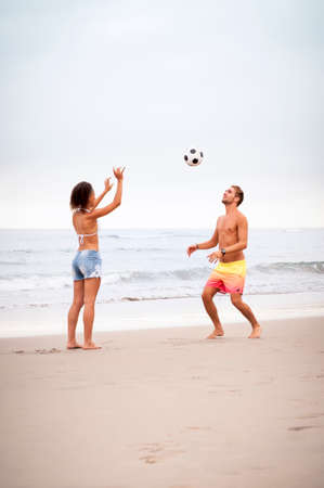 mixed race couple: Young mixed race couple playing on beach with football