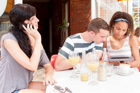 Group of young people talking together over digital tablet at coffee shop Stock Photo - 37211667