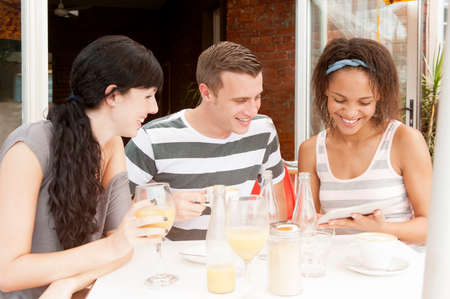 Group of young people talking together over digital tablet at coffee shop