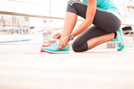 Close up of girl tying her running shoe laces at sunrise