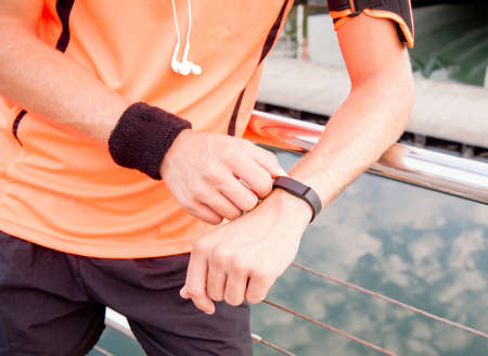 armband: Close up of guy using wearable fitness gear Stock Photo