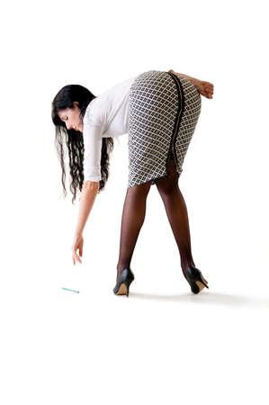 Young beautiful woman reaching down to pick up pencil 版權商用圖片