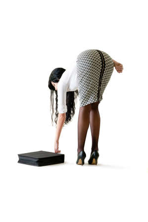 pencil skirt: Young beautiful woman reaching down to pick up attache case