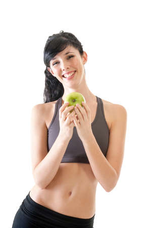 Happy healthy young girl eating a green apple after exercise photo
