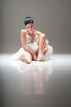 Young attractive ballerina sitting on the floor working with her pointed ballet shoes photo
