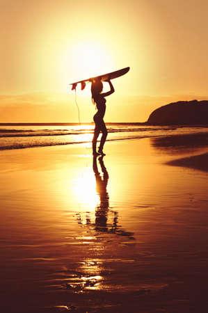 surfer girl standing beach ocean surfboard reflection shore sunrise silhouette photo