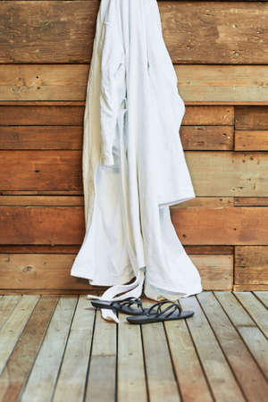 Gown or robe hanging in a Spa with sandals Stock Photo