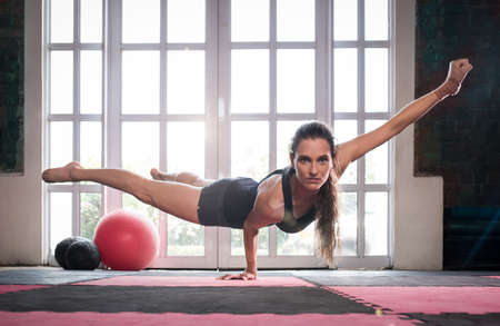 one hand: woman balancing while doing a one hand push up showing strength and determination