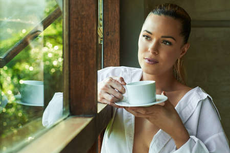 Sexy beautiful woman looking out a window with tea or coffee pondering.