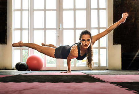 woman balancing while doing a one hand push up showing strength and determination