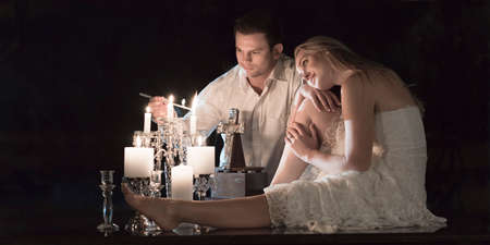 Couple at a candle lit ceremony together.