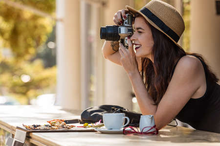 young beautiful traveler happily taking photos with camera at cafe Standard-Bild