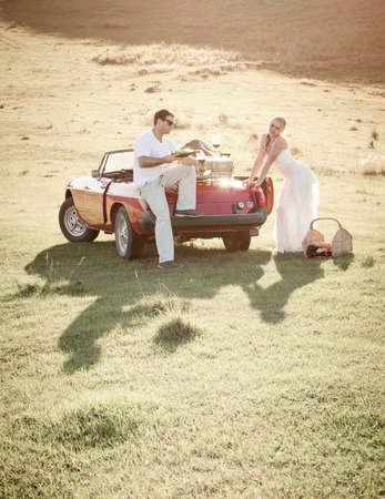 couple in a grass field having a picnic outdoors. Standard-Bild
